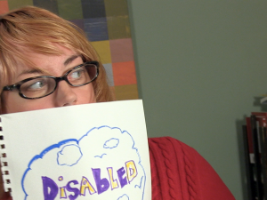 caitlin holding sign reading 'disabled'